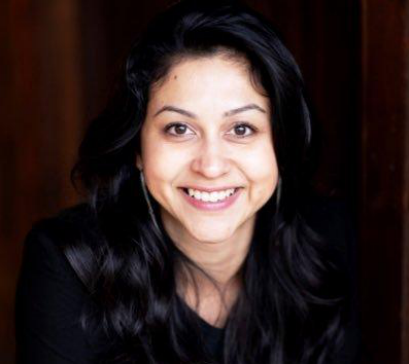 Photo of Neha Narkhede in front of a dark wall.